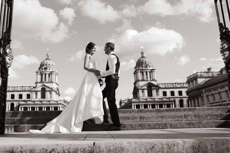 Bride and groom by the River Thames on the steps of the Royal Naval College in Greenwich.