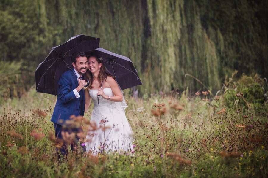 Bride and groom with umbrellas in the Grittenham Barn meadow