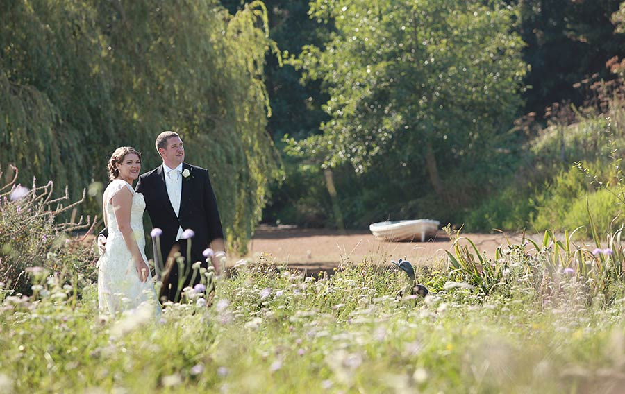 Bride and groom in front of lake at Grittenham-Barn