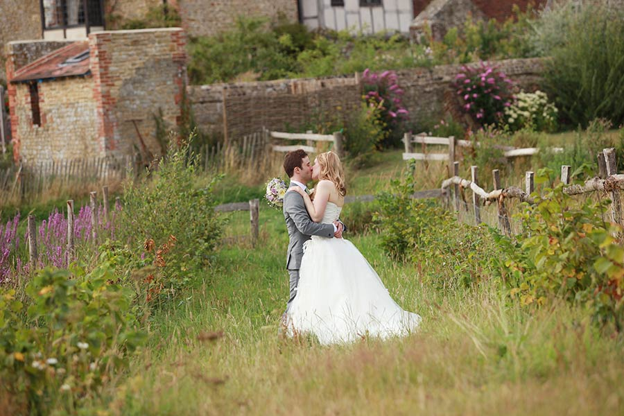 bride and groom kiss in meadow at Grittenham Barn