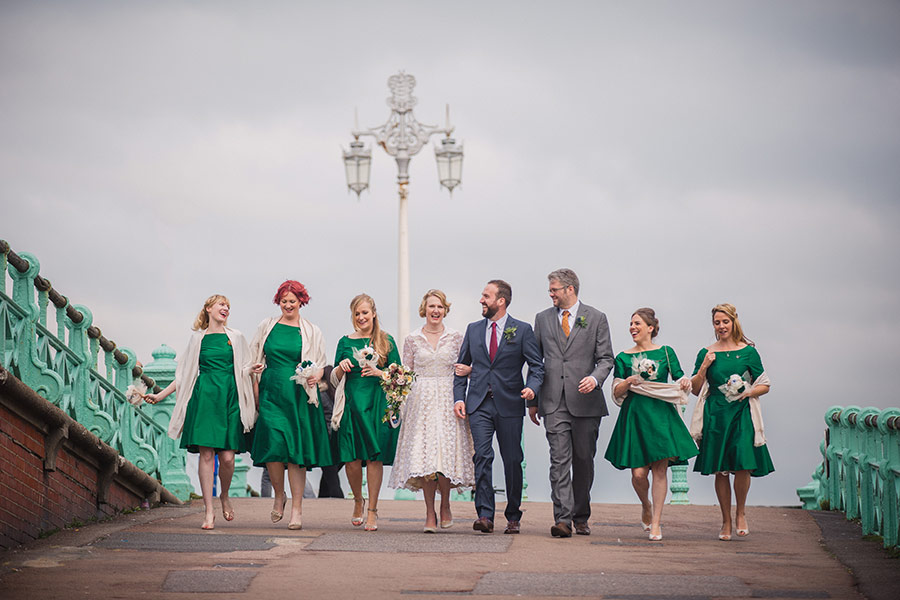 Bride, groom, bridesmaids and best man walking together on Brighton seafront