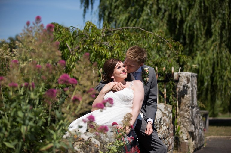 bride and groom sitting on the wall during their coltsford mill wedding