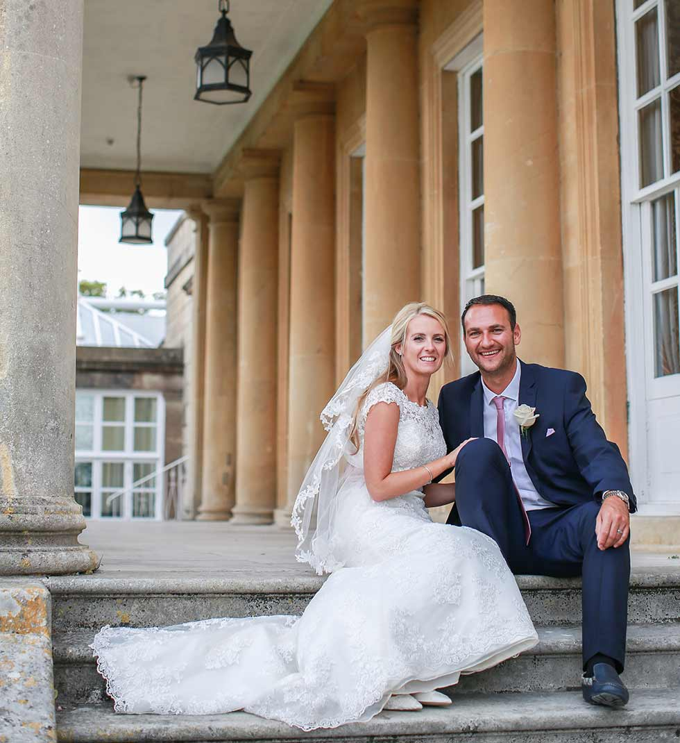 bride and groom sitting under pillars at buxted park