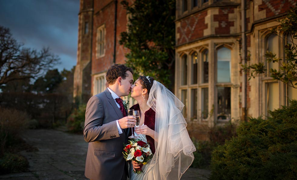 bride and groom kissing in front of horsted place