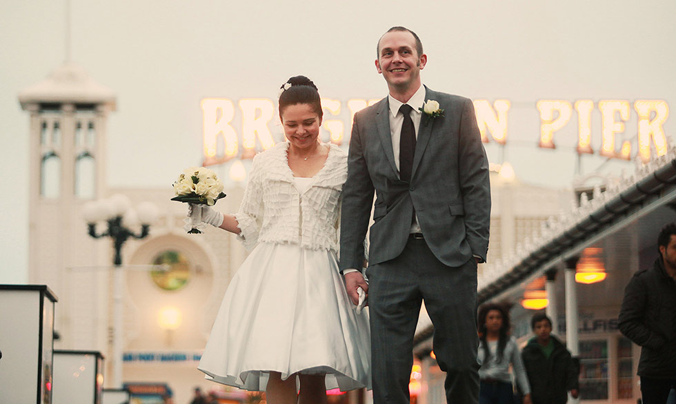 bride and groom walking on Brighton Pier