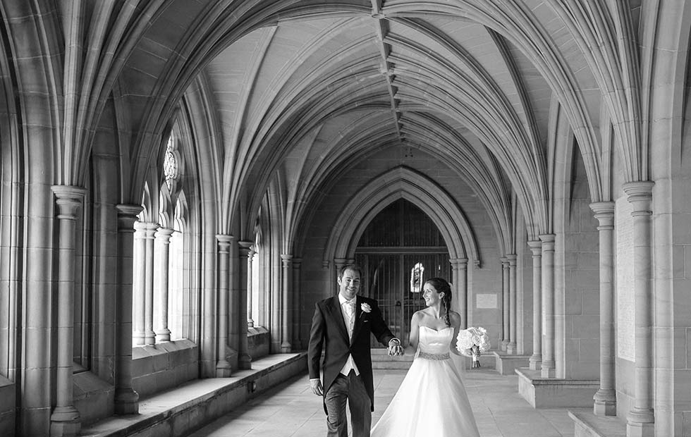 bride and groom walk down lancing college chapel cloisters