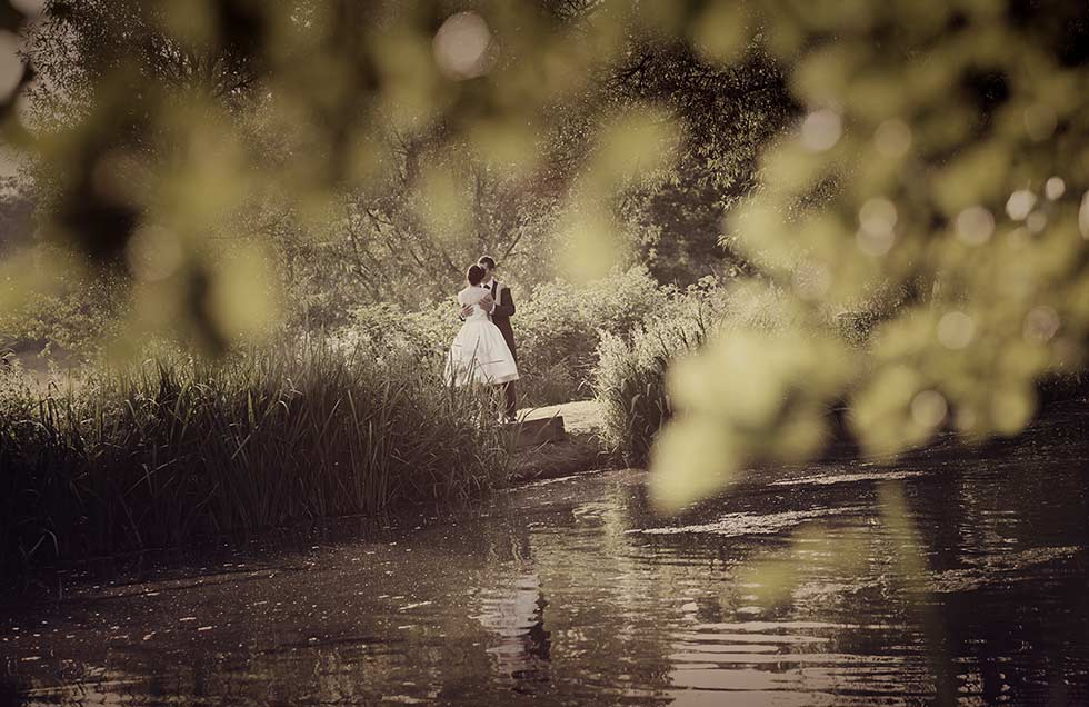 bride and groom kiss by a coltsford mill lake