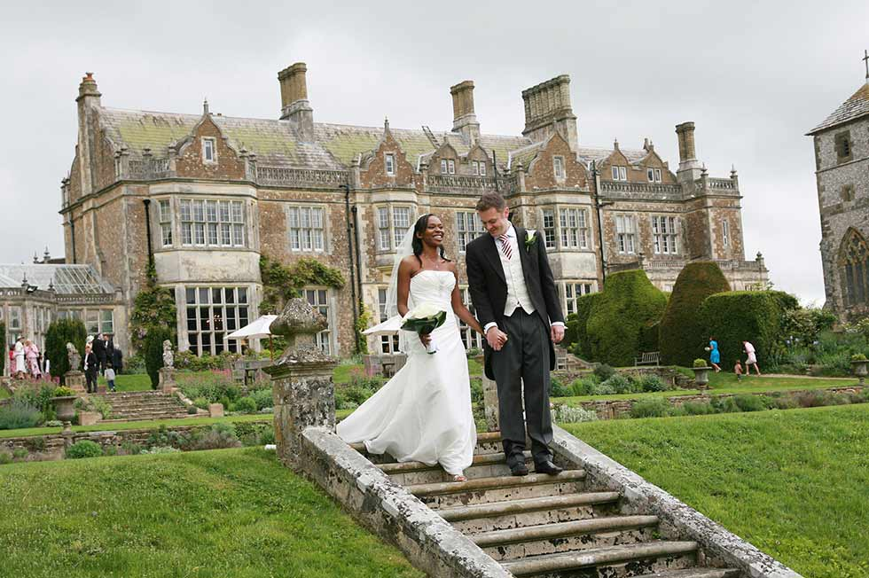 bride and groom walking down steps outside wiston house
