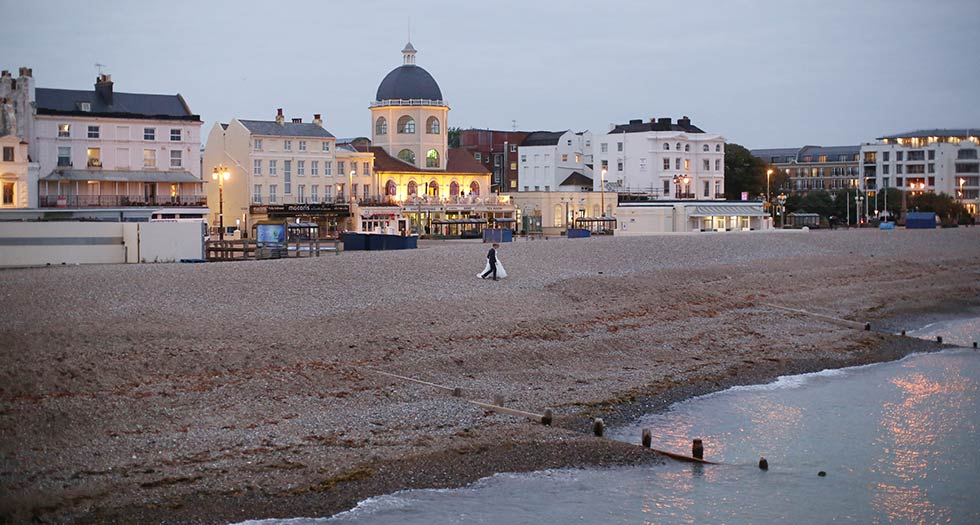 bride and groom on the beach in front of worthing dome