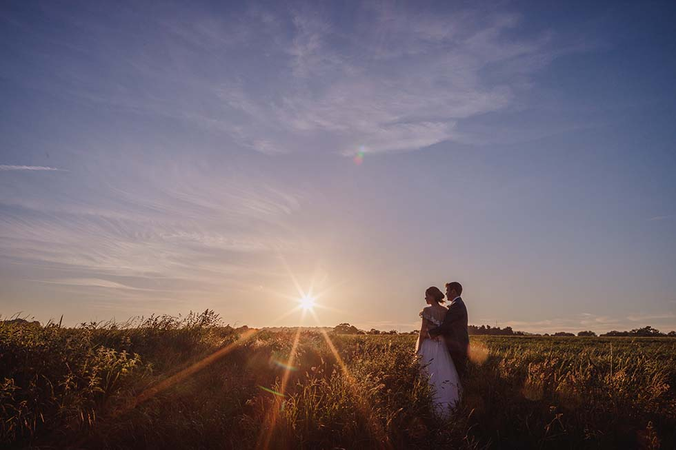 bride and groom look out over fields at Grittenham Barn sunset