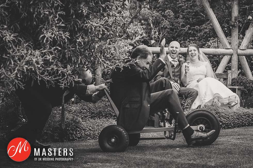 Uncle speeds past on a scooter in front of the bride and groom at Pangdean Barn