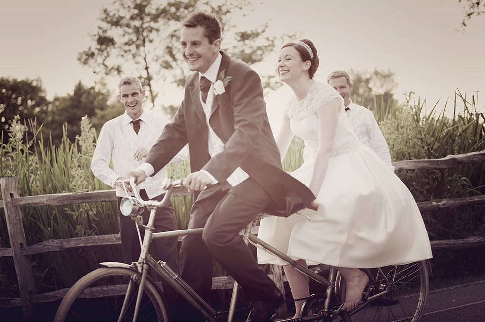 bride and groom on a bike at coltsford mill
