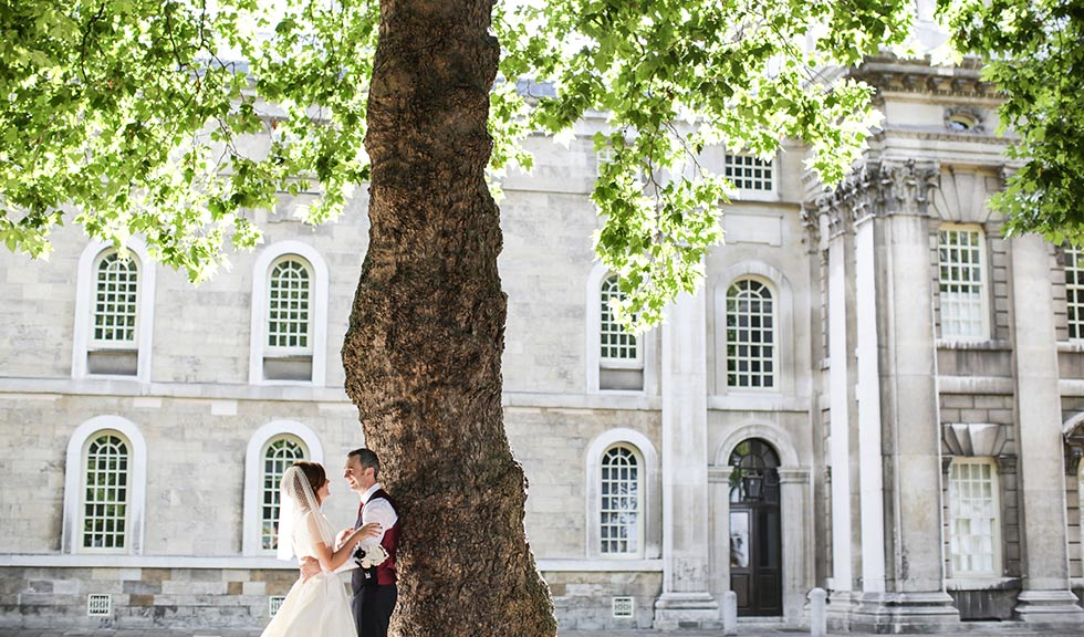 Brighton and groom under a tree outside Greenwich Old Royal Naval College