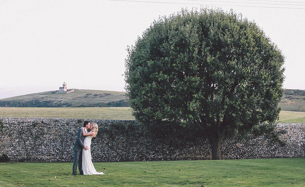 bride and groom kiss at Birling Manor wedding in front of Belle Toute lighthouse