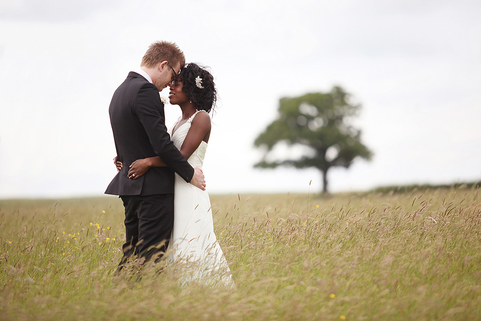 bride and groom caress in a west sussex field of long grass