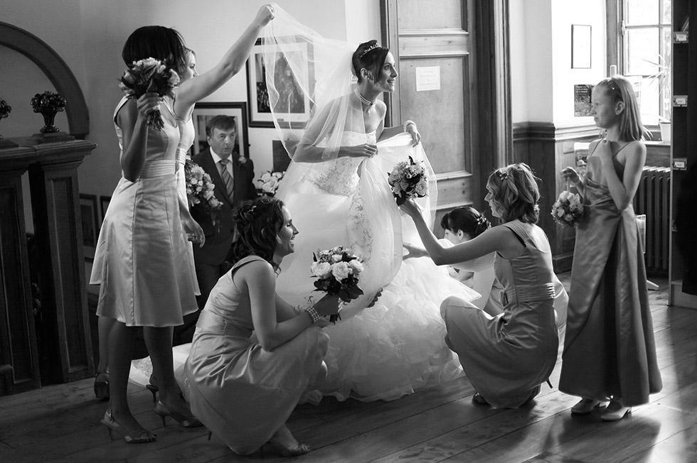 bridal party adjust the bride at Herstmonceux Castle wedding
