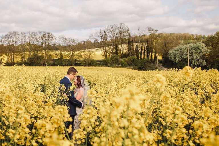 Bride and groom hug in the oil seed rape at Farbridge