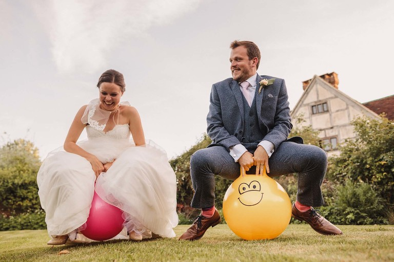 Bride and groom bouncing on space hoppers at Grittenham Barn
