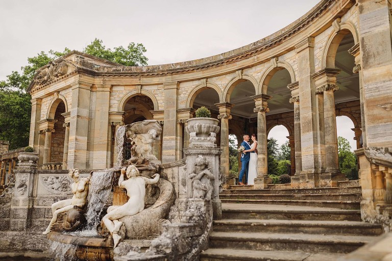 Bride and groom by the Nymph's fountain at the Hever Castle Loggia