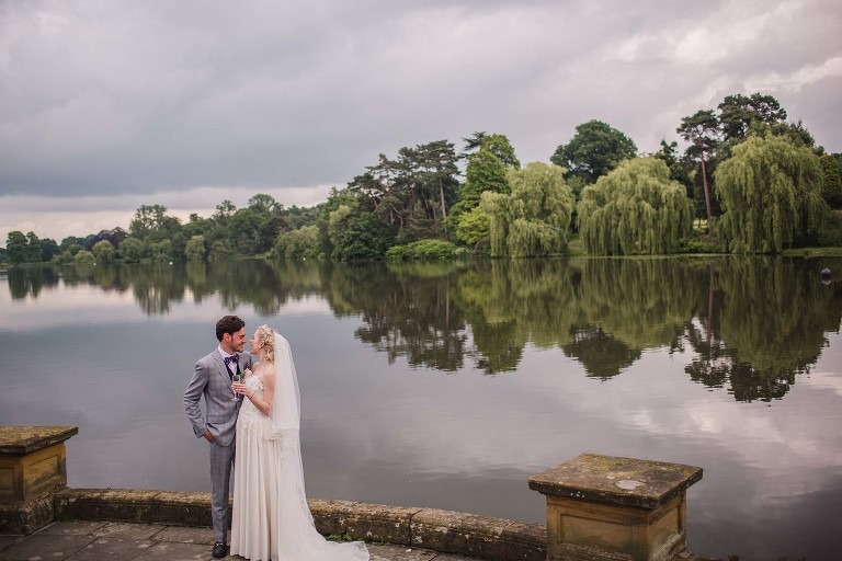 Bride and groom overlooking Hever Castle's lake.