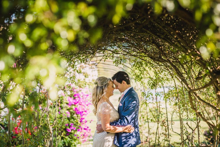 Bride and groom in close embrace under the rose tunnel at Wadhurst Castle