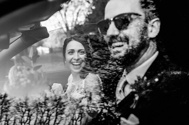 wedding couple in wedding car with trees reflected in windows