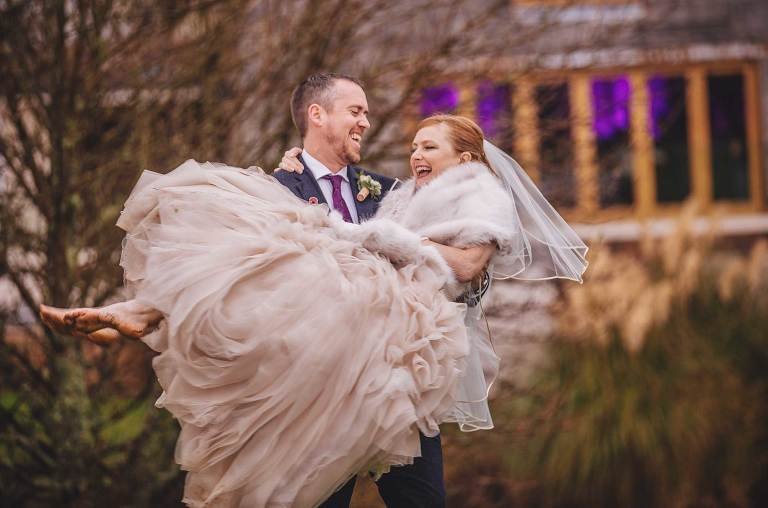 Bride in groom's arms in the rain at Brookfield Barn
