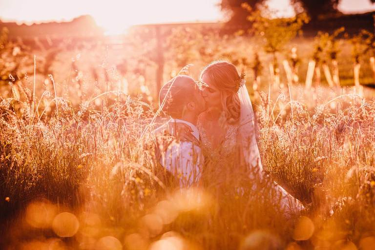 Bride and groom kissing in the grass at golden hour