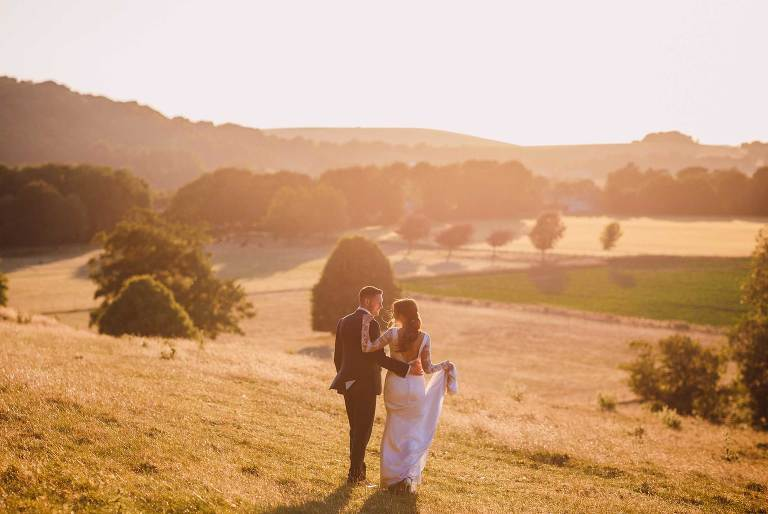 Bride and groom overlooking fields at Cissbury Barns
