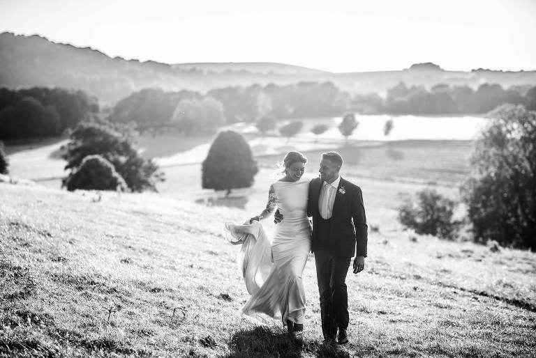 Bride and groom walking up the valley at Cissbury Barns in Sussex