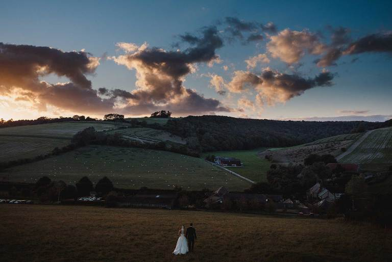 View over Upwaltham Barns wedding venue at sunset with bride and groom in the meadow