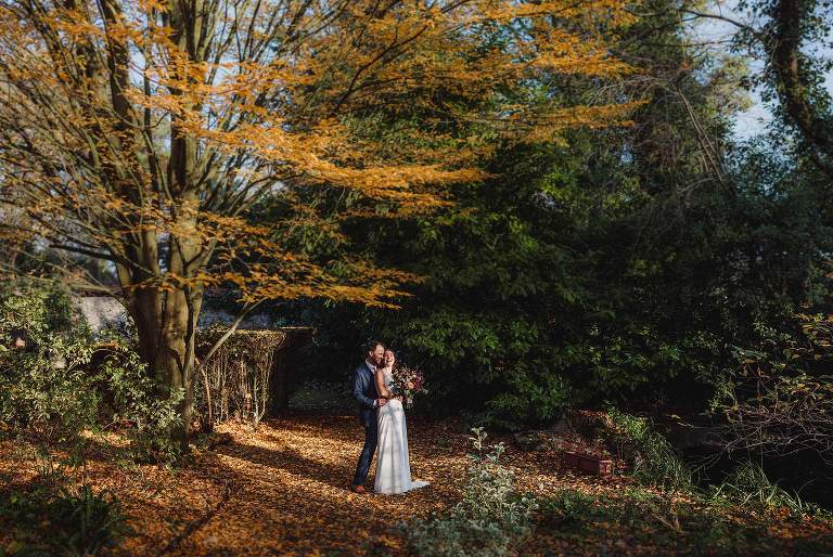 Bride and groom hug amongst the beautiful autumnal tress at St Mary's House Bramber