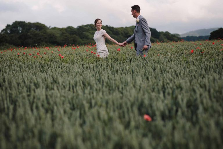 Bride and groom walking hand in hand amongst the wheat at Grittenham Barn wedding venue