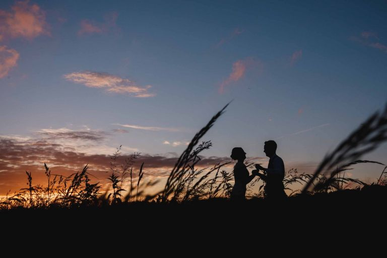 Couple silhouette at sunset in a Grittenham Barn meadow