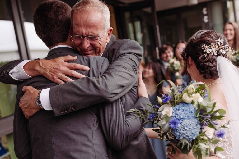 Intense hug from between the groom and the father of the groom at Crawley registry office