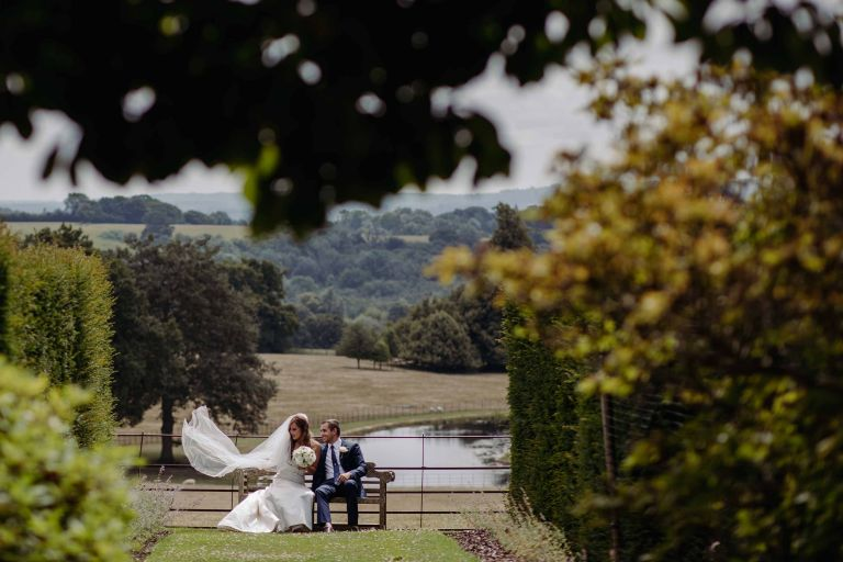 Bride and groom enjoying a quiet moment on a bench at Wadhurst Castle with the lake on view behind them