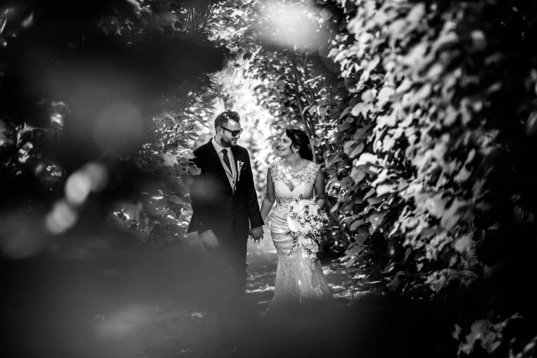Bride and groom walk through the avenue of trees at Grittenham Barn