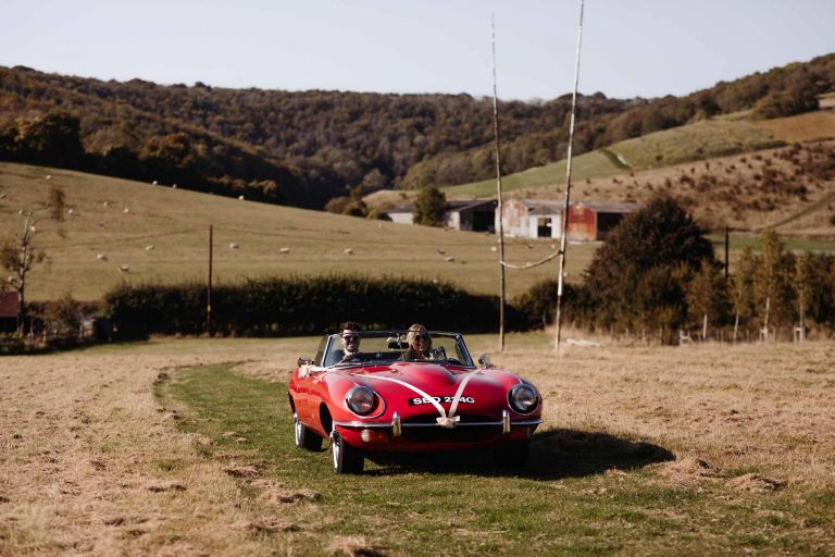 Bride and groom in their wedding vintage S-type Jaguar at Upwaltham Barns