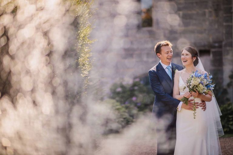bride and groom embrace behind a fountain at Wadhurst Castle