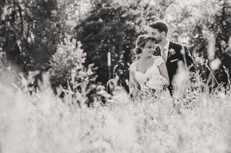 black and white photo of groom kissing bride on the head in the Grittenham Barn meadow