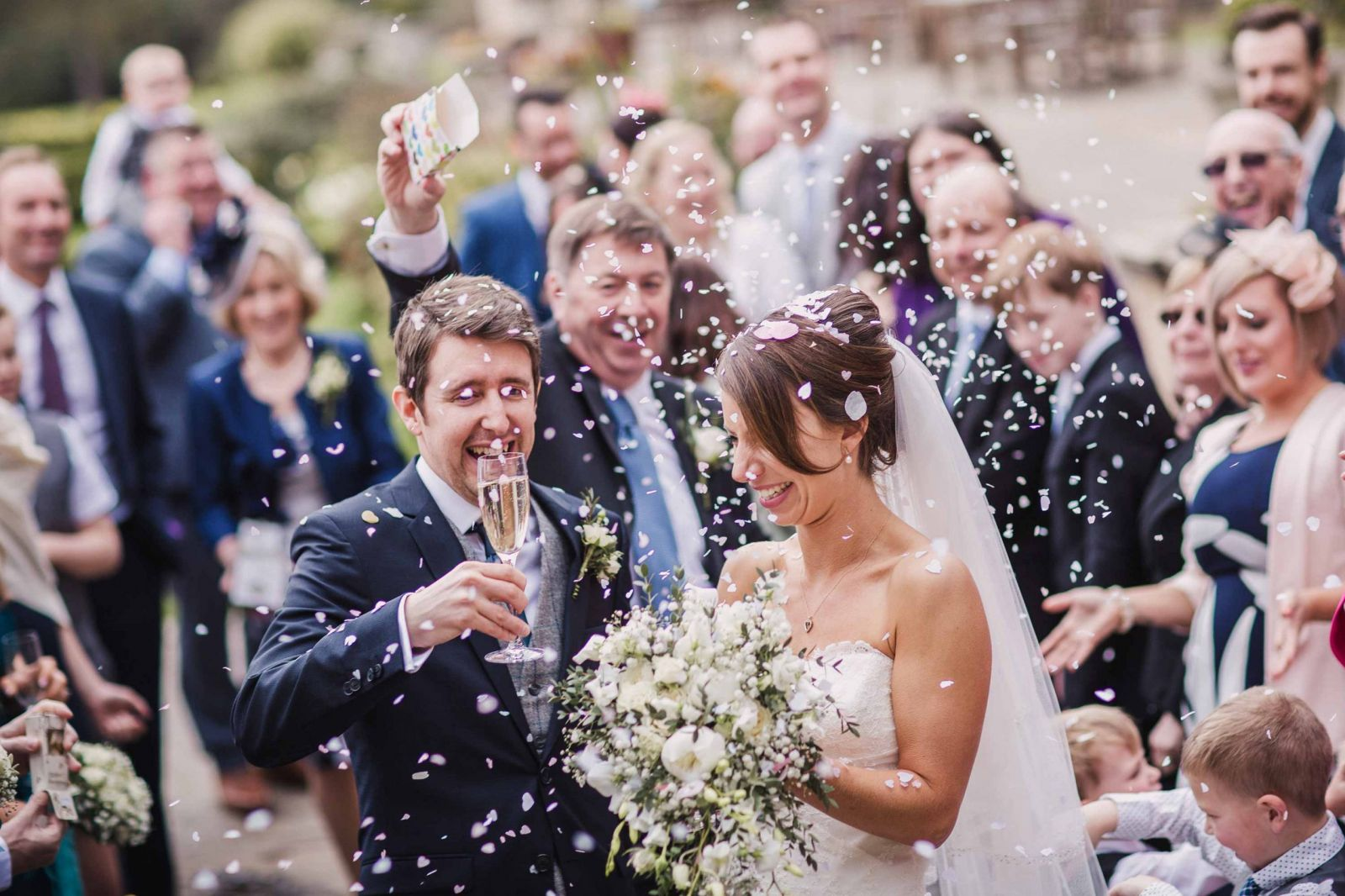 father of the bride throws confetti over bride and groom
