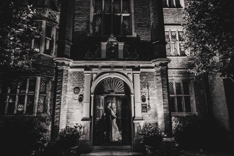 Black and white image of bride and groom embracing at the door of Great Fosters wedding venue