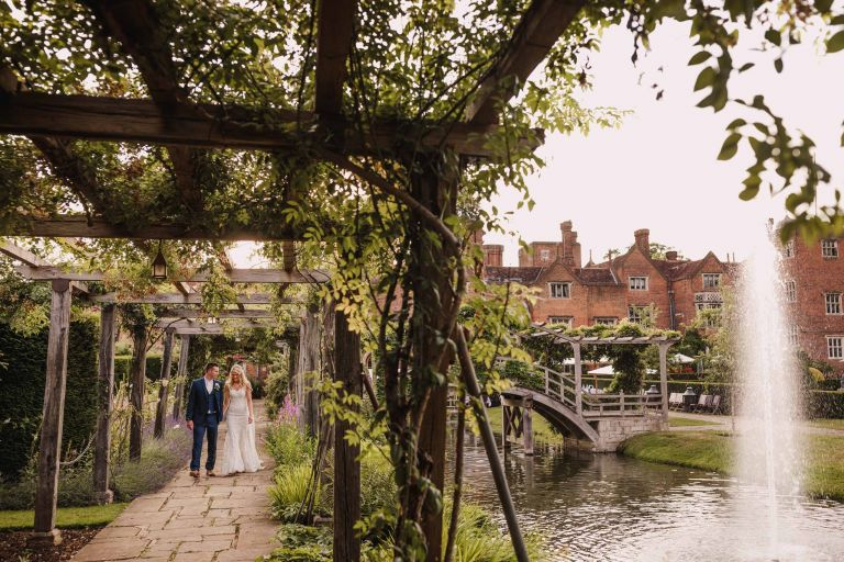 Wedding couple walk in the grounds of Great Fosters