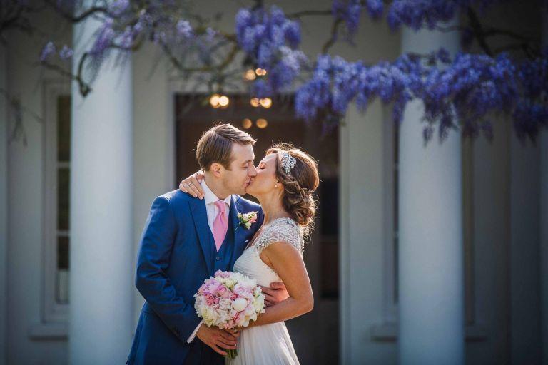 Wedding couple kiss outside Pembroke Lodge in Richmond Park