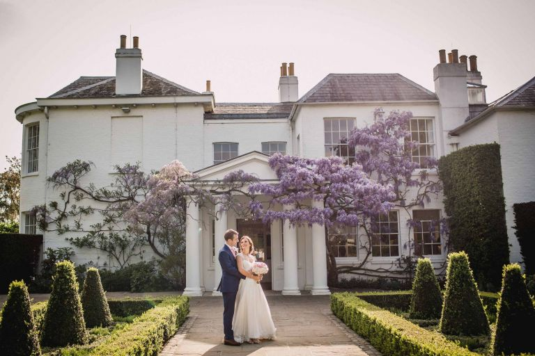 Bride and groom embrace at the front of Pembroke Lodge in Richmond Park