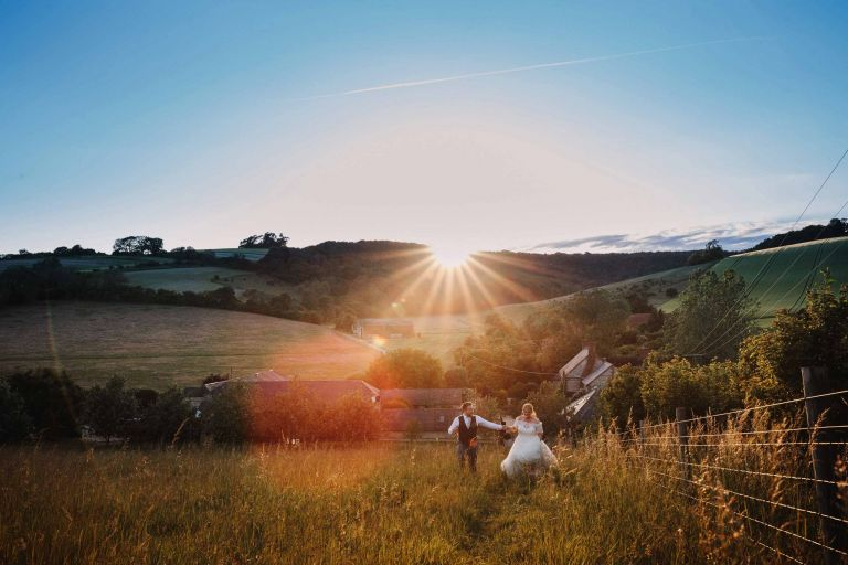 Bride and groom in the Upwaltham Barns meadow on the South Downs at sunset