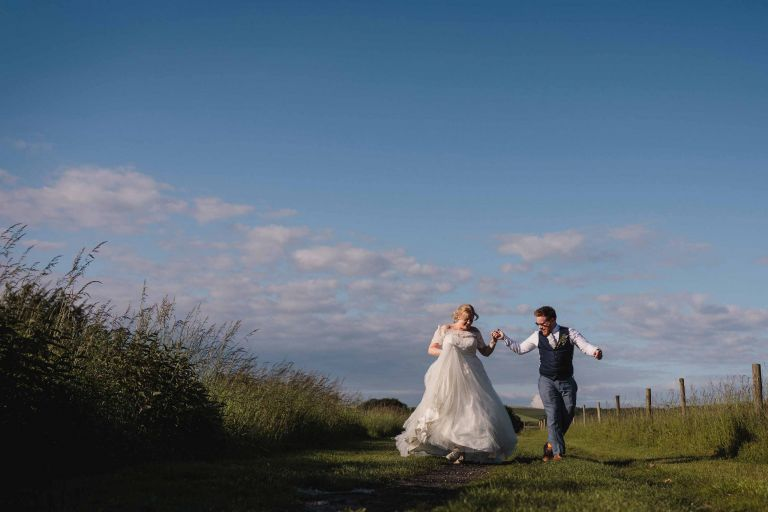 Bride and groom dance outside on the track at Upwaltham Barns