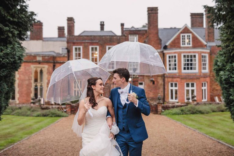 Bride and groom with umbrellas at rainy Wotton House wedding
