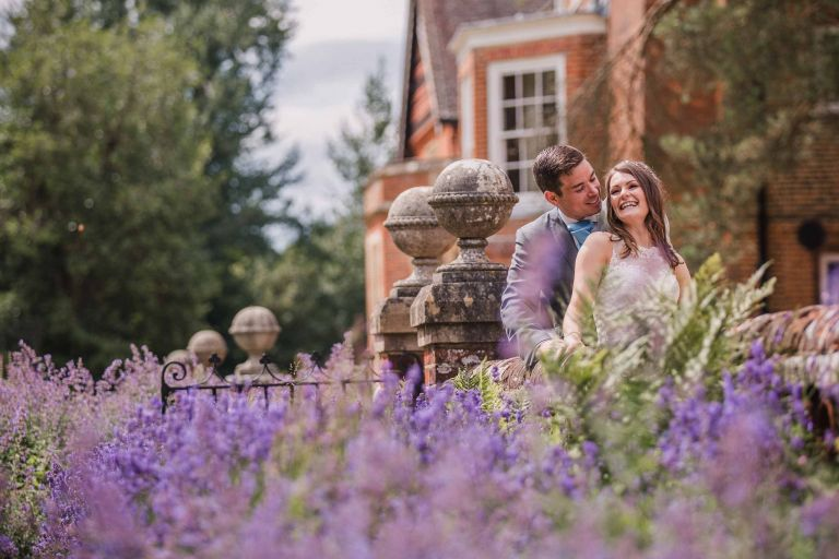Bride and groom laughing in the lavender at Wotton House
