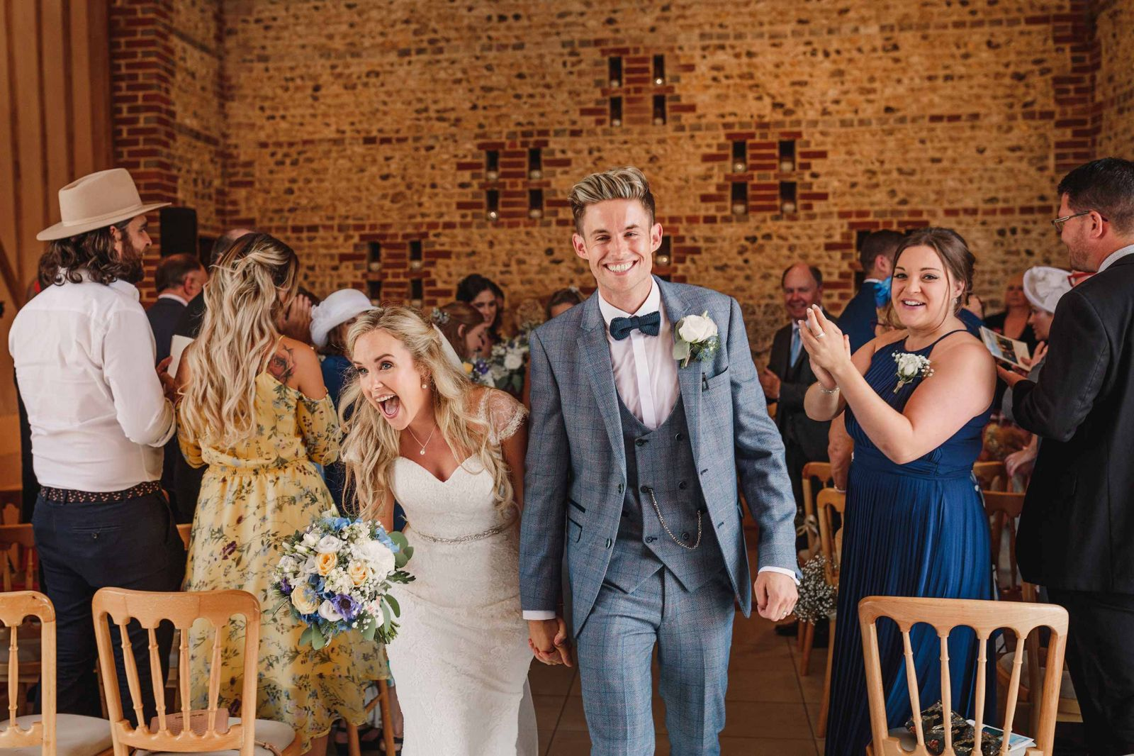 Bride and groom walk down the aisle after their Upwaltham Barn wedding ceremony